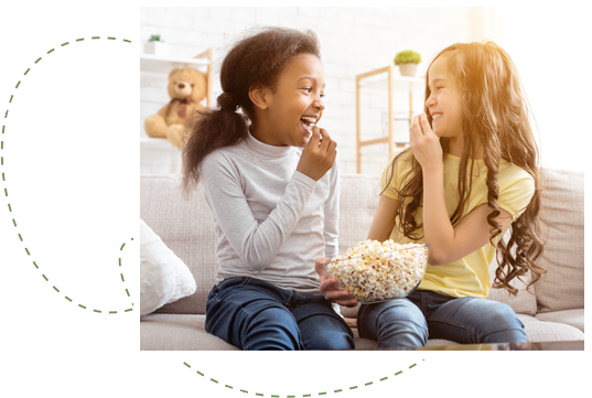 Two young girls happily sharing a bowl of popcorn